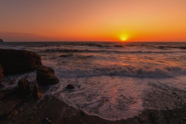 Tempestade em uma costa rochosa ao pôr do sol
