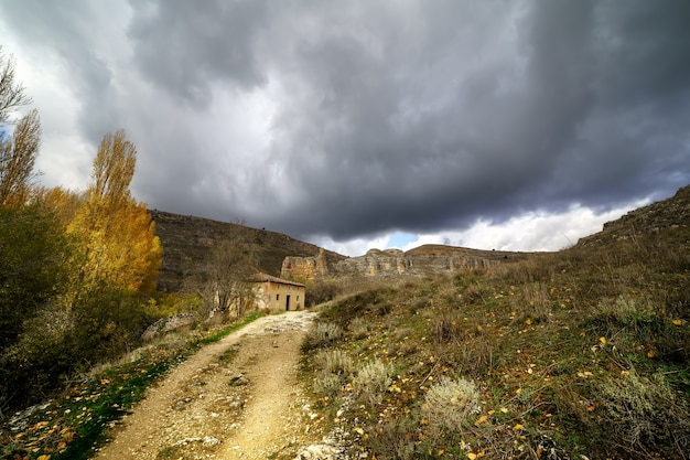 Tempestade no céu com nuvens negras, paisagem de outono, estrada e pequena casa.