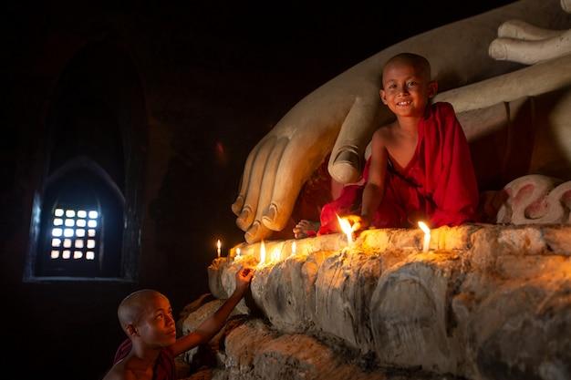 Templo de monge rezando para uma estátua de buda com velas