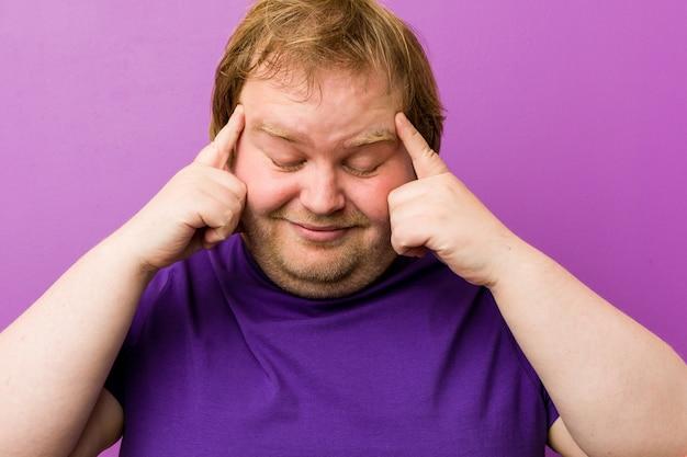 Templos tocantes do homem gordo autêntico novo do ruivo e ter a dor de cabeça.
