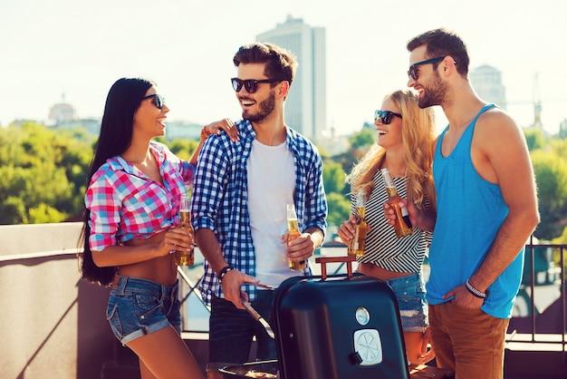 Tempo alegre com amigos. grupo de jovens alegres segurando garrafas com cerveja e fazendo churrasco em pé no telhado