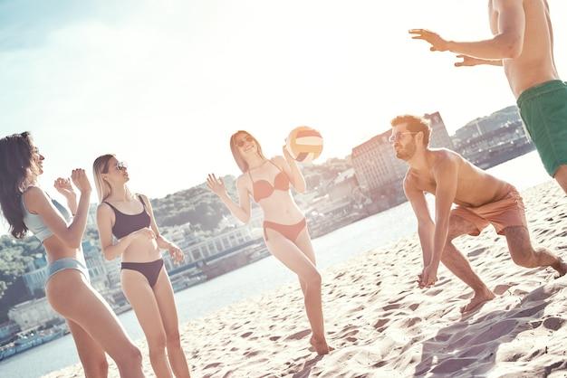 Tempo com grupo de amigos de jovens jogando vôlei na praia