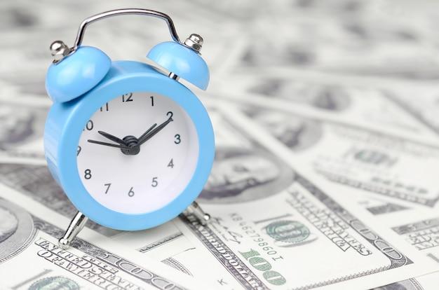 Tempo como um importante recurso comercial. despertador azul e notas de dólar
