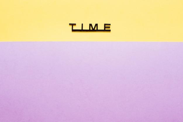 Tempo da palavra em letras pretas em um fundo de papel colorido