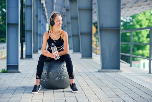 Tempo de água. mulher levando estilo de vida saudável água potável antes de exercitar-se na bola de fitness