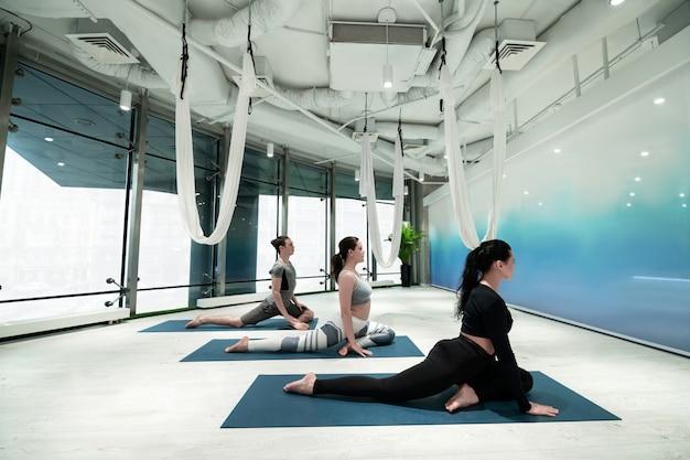 Tempo de alongamento. duas mulheres ativas e em forma e um homem esticando as pernas enquanto fazem ioga juntos