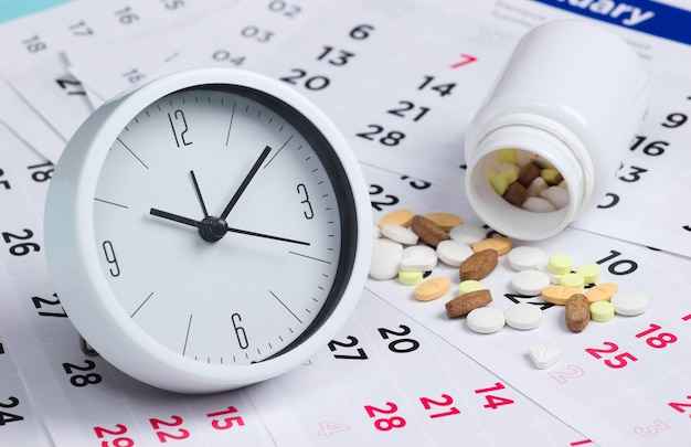 Tempo de controle para tomar comprimidos. relógio com um frasco de comprimidos em um calendário mensal