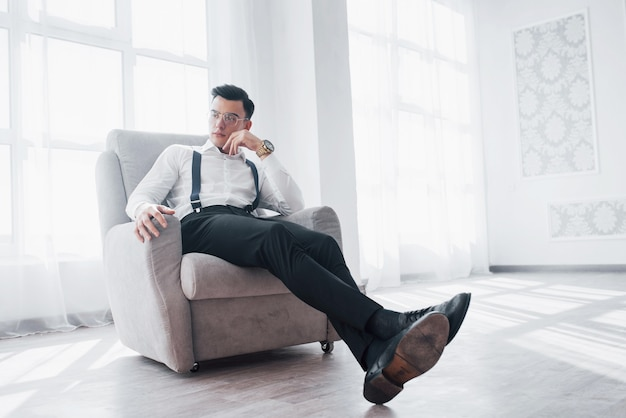 Tempo de descanso. foto de cara atraente de óculos e desgaste elegante, sentado na cadeira.
