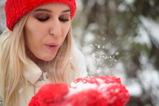Tempo de inverno feliz andando na rua. aproveitando a queda de neve, expressando positividade, sorrindo para a câmera, alegre, alegre, clima de ano novo