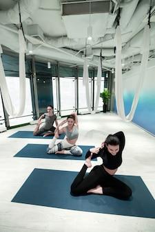 Tempo de ioga. vista superior de duas mulheres e um homem fazendo ioga em esteiras esportivas juntos