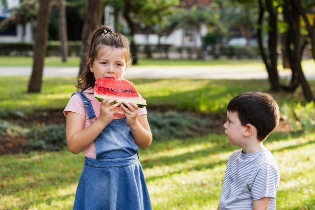 Tempo de irmãos na natureza e garota comendo melancia