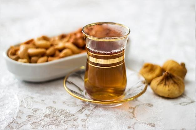 Tempo de lanche com xícara de chá, figos e caju