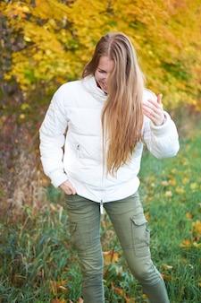 Tempo de outono. retrato de jovem rindo menina positiva com cabelo comprido natural bonito vestindo jaqueta branca e calça verde. árvores de outono amarelas sobre fundo.
