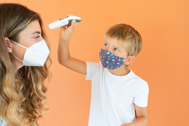 Tempo de pandemia e conceito de saúde, filho ou aluno medindo temperatura para sua mãe ou professor com temometr sem contato, família, educação e saúde social