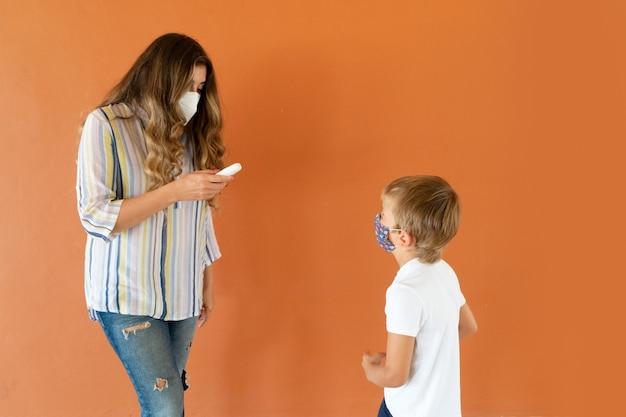 Tempo de pandemia e conceito de saúde, mãe ou professor medindo a temperatura para seu filho ou aluno com temometr sem contato e observando o resultado, família, educação e saúde social