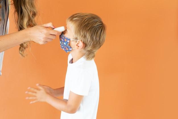 Tempo de pandemia e conceito de saúde, mãe ou professor medindo a temperatura para seu filho ou aluno com temometr sem contato, família, educação e saúde social
