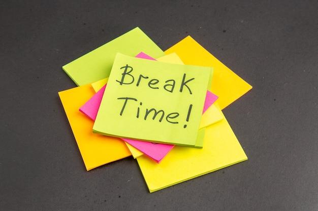 Tempo de pausa da vista inferior escrito em notas adesivas rosa e amarelas na parede escura