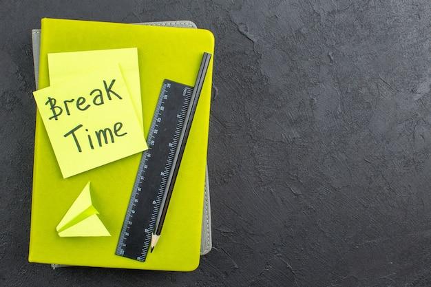Tempo de pausa da vista inferior escrito no lápis preto da régua de notas auto-adesivas em cadernos com fundo escuro