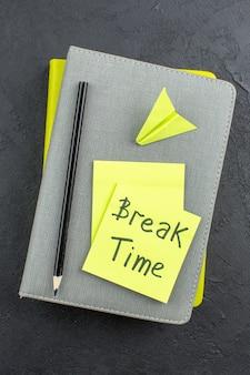 Tempo de pausa da vista superior escrito em notas adesivas amarelas, papel avião, lápis preto em blocos de notas na mesa escura