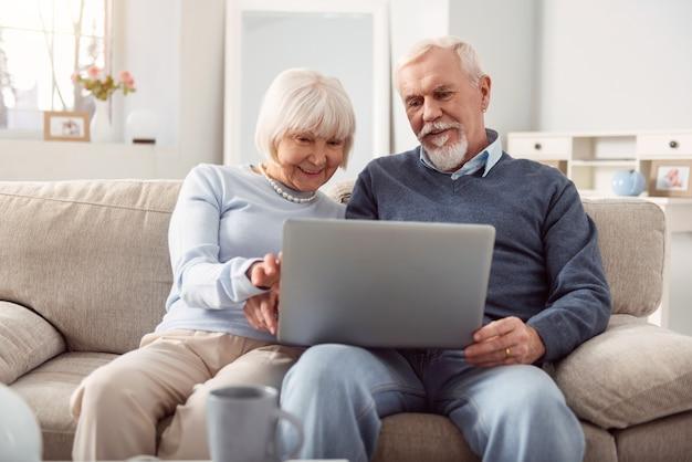 Tempo de qualidade. marido e mulher sênior otimistas segurando um laptop no colo e navegando na internet juntos enquanto estão sentados no sofá da sala de estar