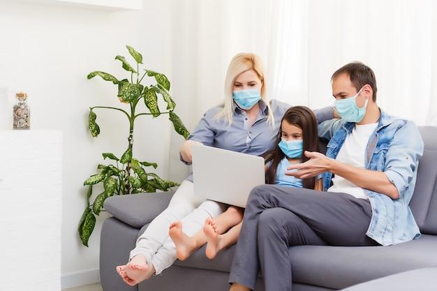 Tempo de quarentena: família com máscaras de proteção na sala de estar junta.