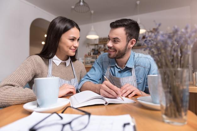 Tempo de trabalho saboroso. ainda bem que feliz casal de proprietários de café sorrindo e fazendo anotações enquanto está sentado bebendo café.