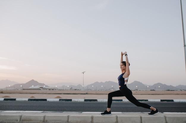 Tempo de treinamento, estendendo-se na estrada num país tropical de mulher bonita alegre na manhã ensolarada. treino de forte desportista, energia, motivação, estilo de vida saudável.