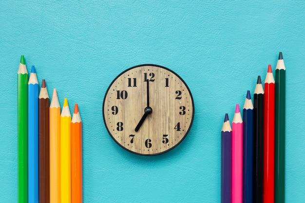 Tempo de volta às aulas com relógio e lápis de cor