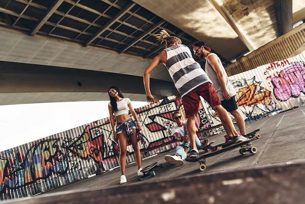 Tempo despreocupado com os amigos. comprimento total de jovens modernos com patins andando juntos ao ar livre