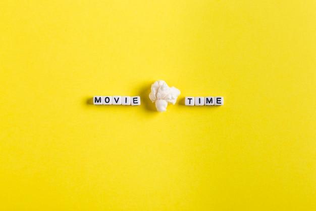 Tempo do filme escrito em blocos sobre um fundo amarelo e com uma pipoca. conceito de plano de filme