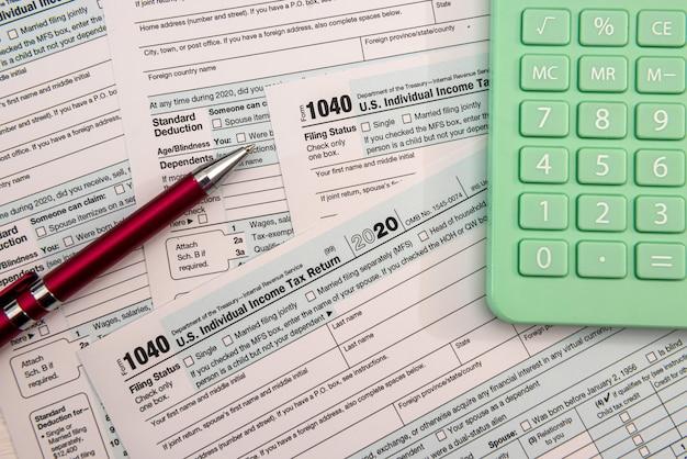Tempo do imposto 2021 - 1040 arquivo caneta-tinteiro e calculadora, papelada