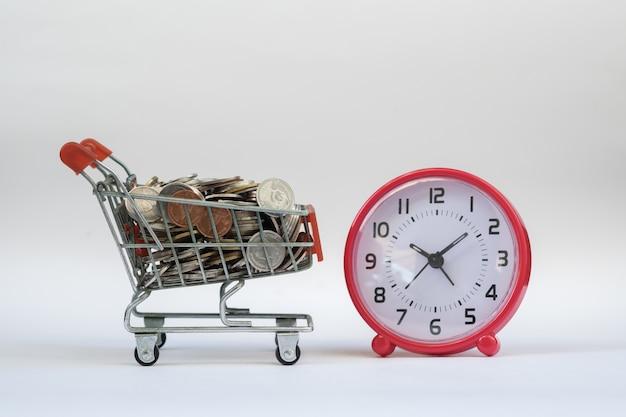 Tempo, e-commerce e conceito de compras. mini carrinho de compras cheio de moedas com despertador