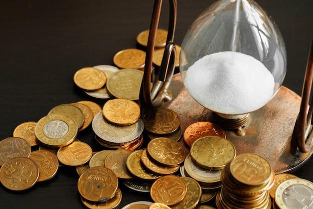 Tempo é dinheiro conceito. de ampulheta com moedas de dinheiro