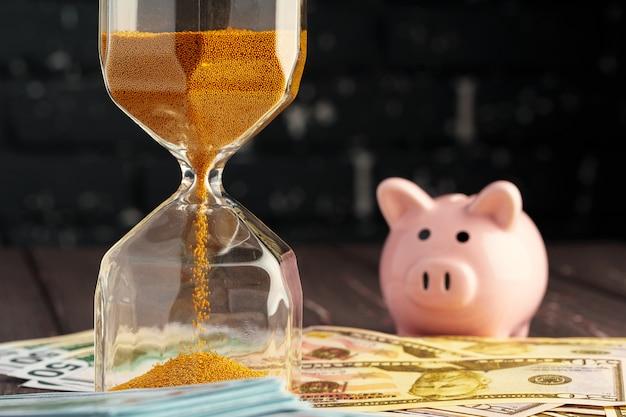 Tempo e dinheiro conceito de negócio. ampulheta e dinheiro