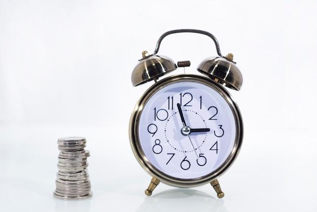 Tempo é dinheiro conceito: despertador e com moedas