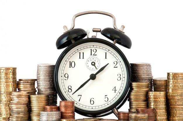 Tempo é dinheiro conceito: despertador e muitas moedas de euro