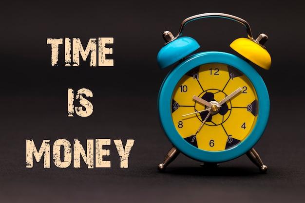 Tempo é dinheiro escrito com despertador em fundo de papel preto.