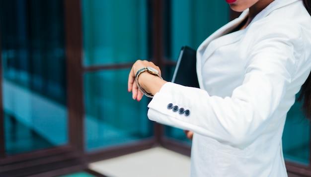 Tempo é dinheiro. mulher de negócios olhando para o relógio de pulso no centro de negócios