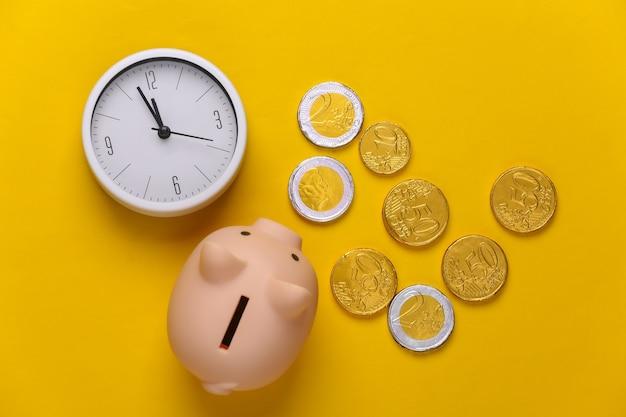 Tempo é dinheiro. relógio branco com cofrinho e moedas em amarelo