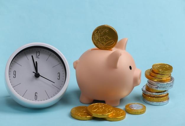 Tempo é dinheiro. relógio branco com cofrinho e pilha de moedas em azul