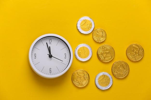 Tempo é dinheiro. relógio branco com moedas amarelas