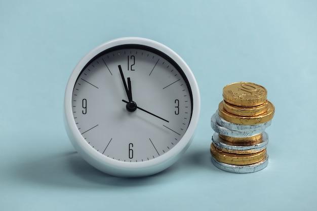 Tempo é dinheiro. relógio branco com uma pilha de moedas em um azul