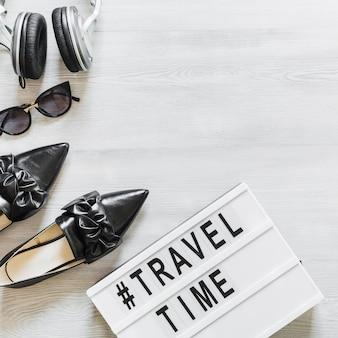 Tempo e texto de viagem com calçado, óculos e fone de ouvido na mesa