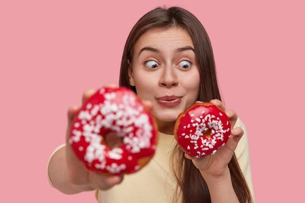 Tempo engraçado com comida. mulher morena elegante e surpresa comendo rosquinhas deliciosas, parece com espanto e diversão