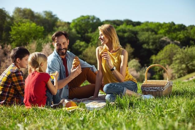 Tempo ensolarado. atraente mãe alerta sorrindo e fazendo piquenique com a família