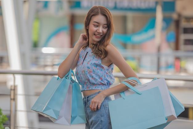 Tempo feliz ao conceito de compra, mulher asiática que guarda sacos de compras no centro da alameda.