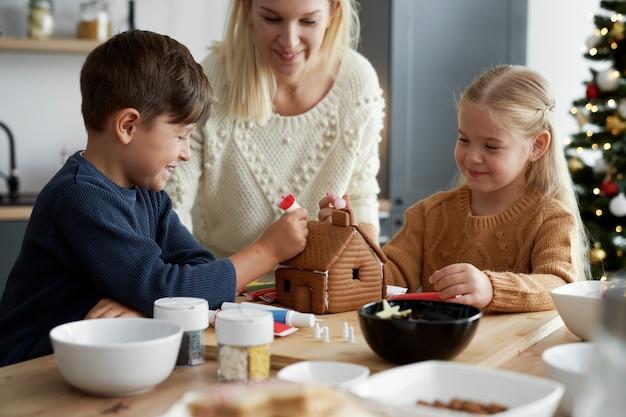 Tempo feliz em família decorando casa de pão de gengibre