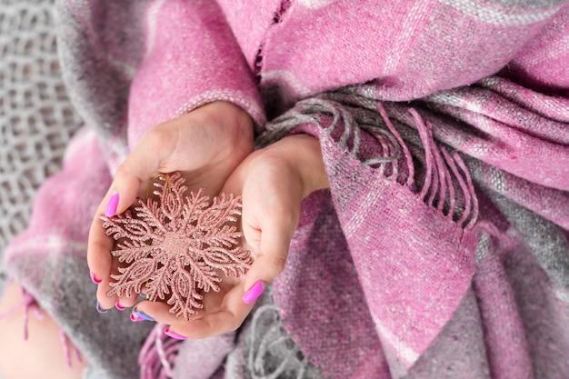 Tempo festivo de inverno aconchegante. mulher segurando um floco de neve brilhante ouro rosa com as mãos cobertas por um cobertor quente