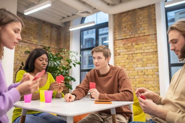 Tempo livre, brinque. jovens focados e pensantes sentados à mesa, jogando cartas com interesse no escritório da organização juvenil