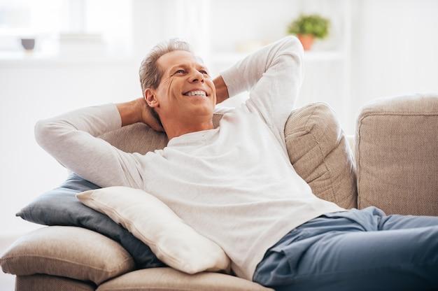 Tempo livre em casa. homem maduro alegre de mãos dadas atrás da cabeça enquanto está deitado no sofá em casa